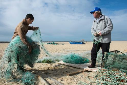 Kuva: Pilvikki Kause Kalastajakylä Aguda, Portugali Diogo Campota auttoi isoisä Carlos Campotaa verkkojen putsauksessa Agudan kylässä. Ammattikalastaja harmitteli meressä lilluvan roskan määrää, muttei ollut vielä koskaan perannut kalan sisästä muovia.