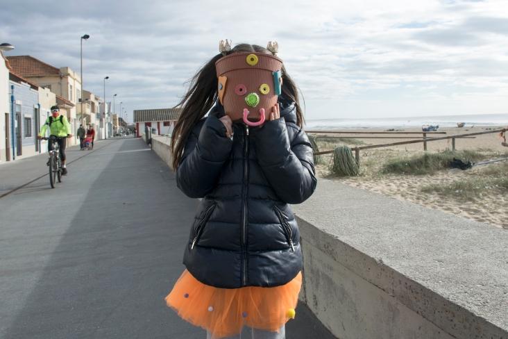 Mariana Aparício askarteli itselleen naamion rannalta kerätystä muoviroskasta Agudan kalastajakylässä.